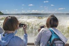 Toeristen die Foto's van Duivelskeel nemen bij Iguazu-Park Royalty-vrije Stock Afbeeldingen
