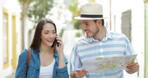 Toeristen die gids raadplegen en telefoon uitnodigen stock footage