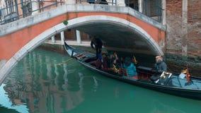 Toeristen die in Gondel langs het Waterkanaal varen stock videobeelden