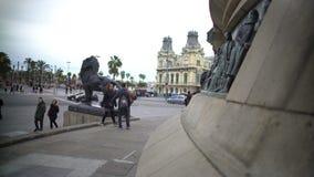 Toeristen die het beeldhouwwerk van de bronsleeuw bekijken bij Columbus Monument-basis in Barcelona stock videobeelden