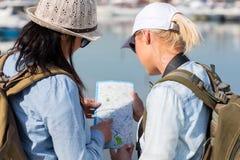 Toeristen die kaart bekijken Stock Foto's