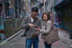 Toeristen die kaart op digitaal apparaat gebruiken Royalty-vrije Stock Fotografie