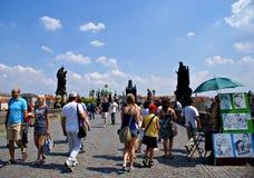 Toeristen die langs Charles Bridge in Praag, Tsjechische Republiek lopen Stock Afbeeldingen
