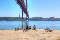 Toeristen die onder de beroemde brug van 25 van April zitten Royalty-vrije Stock Fotografie