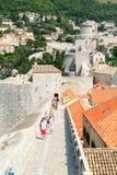 Toeristen die op de stadsmuren lopen van Dubrovnik Stock Foto