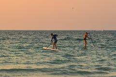 Toeristen die op het overzees bij zonsondergang kayaking stock afbeeldingen