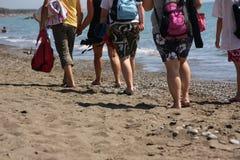 Toeristen die op strand lopen stock afbeeldingen