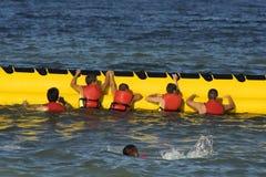 Toeristen die pret met banaan hebben bij de kust stock foto