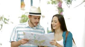 Toeristen die raadplegend een gids over vakantie lopen stock footage