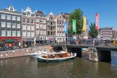 Toeristen die sightseeingsreis maken door lanceringsschip in de kanalen van Amsterdam stock fotografie