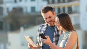 Toeristen die telefoon en document gids vergelijken stock videobeelden