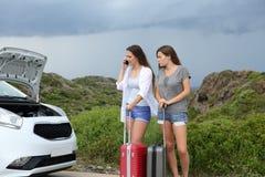 Toeristen die verzekering over een versleten auto roepen stock fotografie