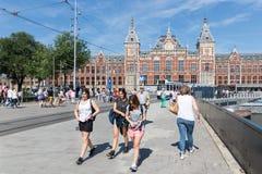 Toeristen die voor de centrale post van Amsterdam lopen Royalty-vrije Stock Afbeeldingen