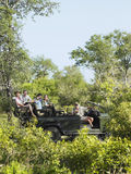 Toeristen en Bestuurder In Jeep On Safari royalty-vrije stock foto