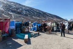 Toeristen en het drijven markt met zwarte berg op de achtergrond in de winter bij Op het absolute nulpunt in Lachung Noord-Sikkim Stock Fotografie
