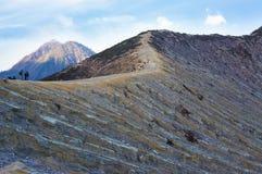 Toeristen en mijnwerkers die op Ijen-vulkaan lopen Royalty-vrije Stock Foto