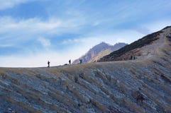 Toeristen en mijnwerkers die op Ijen-vulkaan lopen Royalty-vrije Stock Foto's