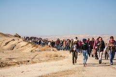 Toeristen en pelgrimsgang door de woestijn Stock Foto