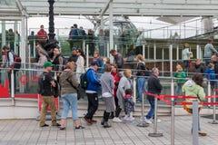 Toeristen in het wachten rij voor het bezoeken van het Oog van Londen, Londen Englan Stock Afbeelding