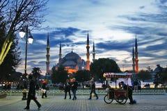 Toeristen in Istanboel bij zonsondergang met blauwe moskee op achtergrond Stock Afbeeldingen