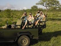 Toeristen in Jeep Looking Through Binoculars stock foto
