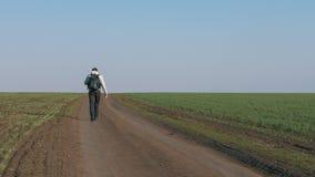 Toeristen jong mannetje die op een landweg door een groen gebied lopen stock footage