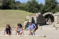 Toeristen klaar om in Olympia, geboorteplaats van het Olympische spel te lopen Stock Foto
