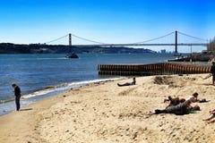 Toeristen op de banken van Tagus-rivier in Lissabon stock afbeelding