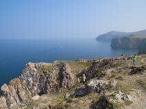 Toeristen op de klippen van het eiland Olkhon Mening van Meer Baikal stock fotografie