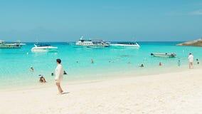 Toeristen op het strand met wit zand Motorboten die bij anker wachten stock footage