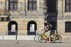Toeristen op huurfietsen bij het Vierkant van de Dam van Amsterdam. Stock Foto's