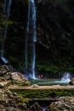Toeristen in reservoir met waterval stock fotografie