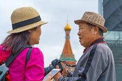 Toeristen van Azië met DSLR-camera en telefoon tegen de Kathedraal van een St Basilicum op Rood Vierkant royalty-vrije stock foto's