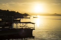 Toeristenboot bij Meerkust wordt tijdens zonsopgang wordt gezien verankerd die Silhouetten Royalty-vrije Stock Foto