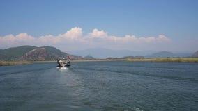 Toeristenboot met vlag die langs riviervideo varen stock footage