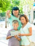Toeristenfamilie die de kaart bekijken Stock Foto