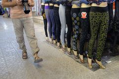 Toeristengangen naast lijn van modellen in legging, Shiraz, Iran stock foto's