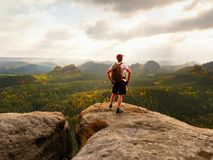 Toeristengids op rotsachtig meningspunt met in hand polen Wandelaar met sportieve rugzaktribune op rots royalty-vrije stock foto's