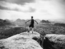 Toeristengids op rotsachtig meningspunt met in hand polen Wandelaar met sportieve rugzaktribune op rots stock fotografie