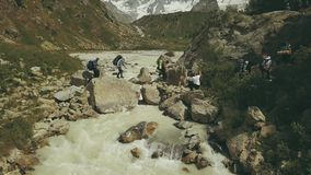 Toeristengroep die de rivier in berg kruisen De luchtrivier van de meningsberg stock video