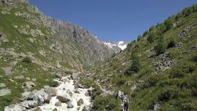 Toeristengroep die op bergsleep lopen langs snelle rivier Het beklimmen van een berg stock video