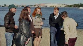 Toeristengroep en gids die op dijk op achtergrond van grote die rivier bespreken door handen wordt geschoten stock videobeelden