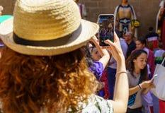 Toeristenmeisje die een beeld met een smartphone van Reuzen en grote hoofden in Catalonië, Spanje nemen royalty-vrije stock fotografie