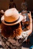 Toeristenmeisje die een beeld met een smartphone van Reuzen en grote hoofden in Catalonië, Spanje nemen stock foto's