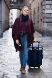 Toeristenmeisje die met de reiszak lopen stock foto