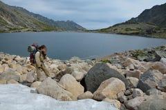 Toeristenmeisje die sneeuw eten dichtbij een bergmeer Stock Foto's