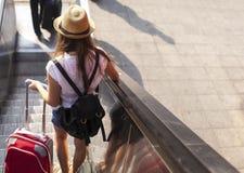 Toeristenmeisje met koffer onderaan de roltrap traveling royalty-vrije stock foto's