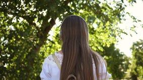 Toeristenmeisje op een stadsstraat met hoofdtelefoons die aan muziek en het glimlachen luisteren tiener die door de straten reize stock videobeelden