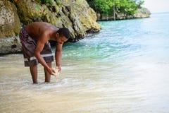 Toeristenmens het spelen met zand op een Caraïbisch strand met oceaan en rotsen op achtergrond royalty-vrije stock fotografie