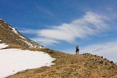 Toeristenmens met een rugzak die zich alleen in snow-capped mo bevinden Stock Afbeelding